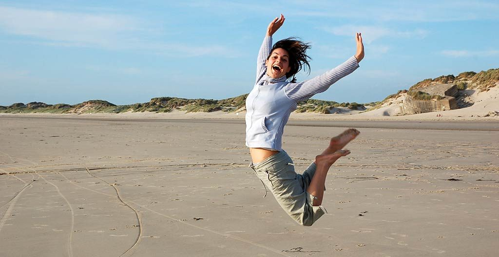 Frau am Strand genießt ihre Freiheit