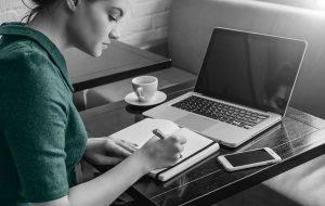Junge Frau sitzt am Rechner und schreibt etwas auf